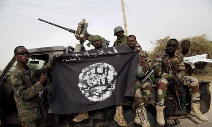 Nigerian soldiers hold up a Boko Haram flag that they had seized in the recently retaken town of Damasak, Nigeria on March 18, 2015. (Reuters/Emmanuel Braun/File Photo)