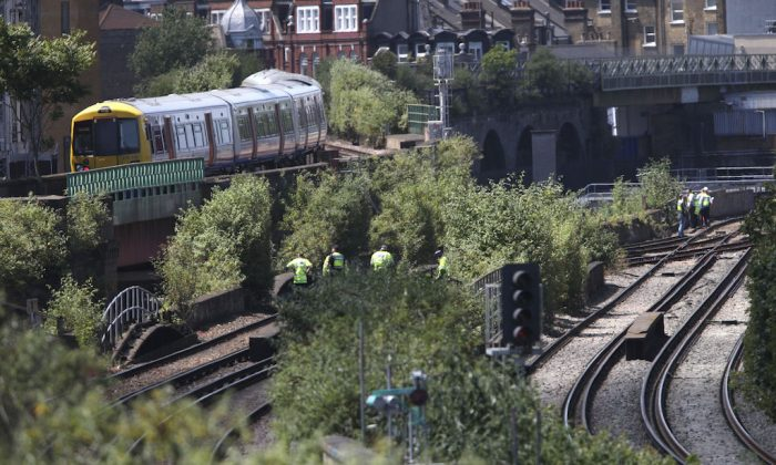 Police officers on a railway track near Loughborough Junction railway station, in south London, Monday June 18, 2018.  (Yui Mok/PA via AP)