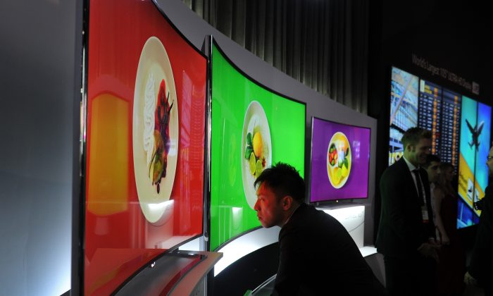 An attendee takes a close look at LG's 105-inch OLED TV at the 2014 International Consumer Electronics Show in Las Vegas, Nevada, on Jan. 8, 2014. (Robyn Beck/AFP/Getty Images)