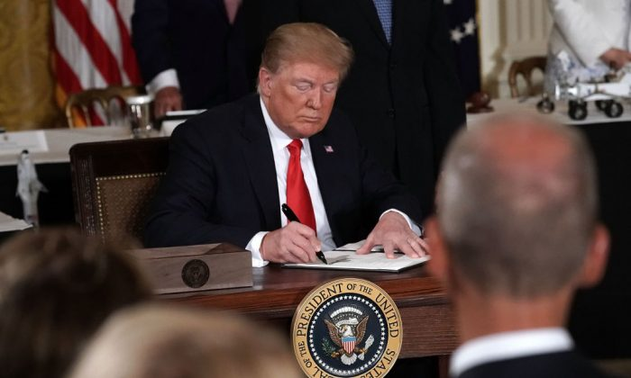 U.S. President Donald Trump signs an executive order during a meeting of the National Space Council at the East Room of the White House June 18, 2018, in Washington, D.C. (Alex Wong/Getty Images)