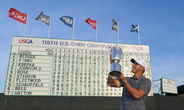 American Brooks Koepka celebrates with the U.S. Open Championship trophy in front of the final leaderboard at Shinnecock Hills Golf Club on June 17, 2018 in Southampton, New York. (Ross Kinnaird/Getty Images)