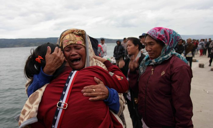 Relatives cry while waiting for news on missing family members who were on a ferry that sank yesterday in Lake Toba, at Tigaras Port, Simalungun, North Sumatra, Indonesia June 19, 2018. (Reuters/Albert Damanik)