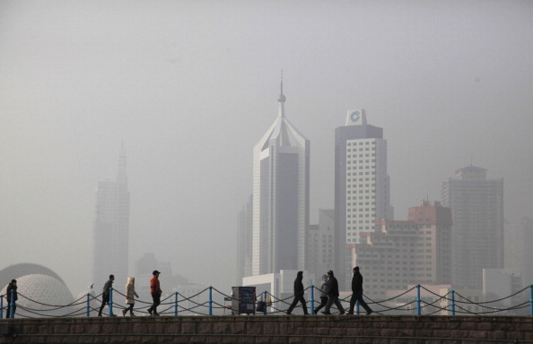 People walk in the heavy smog in Qingdao, a city in eastern China's Shandong Province. (STR/AFP/Getty Images)