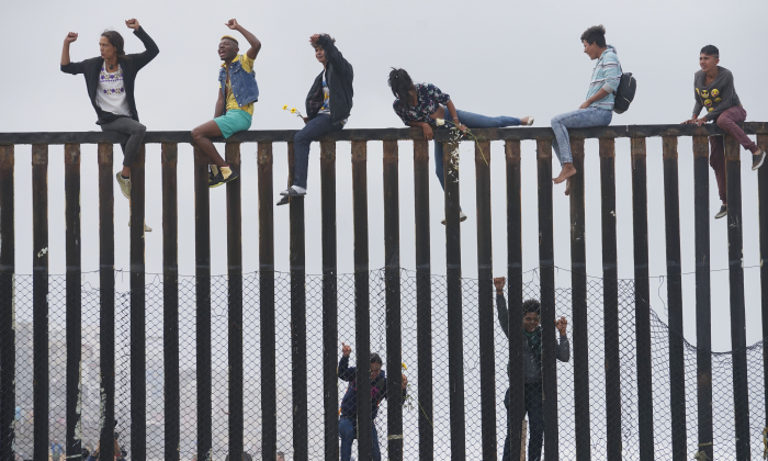 Migrant caravan demonstrators climb the US-Mexico border fence during a rally in San Ysidro, California  on April 29, 2018. (Sandy Huffaker/AFP/Getty Images)