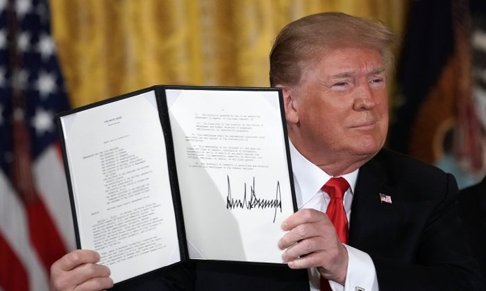 President Donald Trump holds up an executive order for the creation of a Space Force, during a meeting of the National Space Council at the East Room of the White House June 18, 2018 in Washington. (Alex Wong/Getty Images)