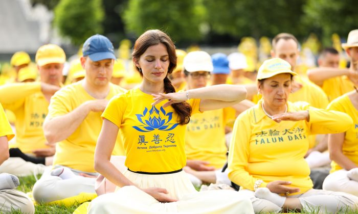 Falun Gong practitioners do their discipline's exercises on the west lawn of the U.S. Capitol on June 20, 2018. (Samira Bouaou/The Epoch Times)