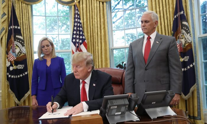 President Donald Trump, accompanied by Department of Homeland Security Secretary Kirstjen Nielsen (L) and Vice President Mike Pence (R), signs an executive order that will end the practice of separating family members who are apprehended after illegally entering the United States, in Washington on June 20, 2018. (Win McNamee/Getty Images)