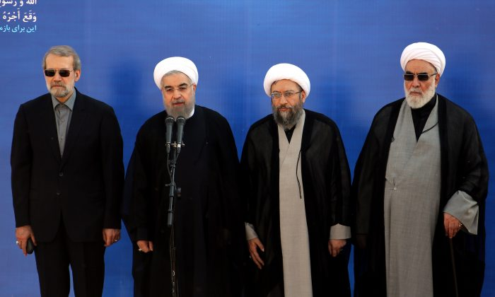 Iranian President Hassan Rouhani (2nd-L) on October 3, 2015 at Tehran's Mehrabad Airport. Large-scale protests in Iran are now calling for an end to the regime. (Atta Kenare/AFP/Getty Images)