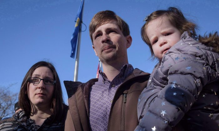 Edouard Maurice, centre, speaks to reporters outside court while holding his daughter Teal as his wife, Jessica, looks on in Okotoks, Alta., on March 9, 2018. (THE CANADIAN PRESS/Jeff McIntosh)