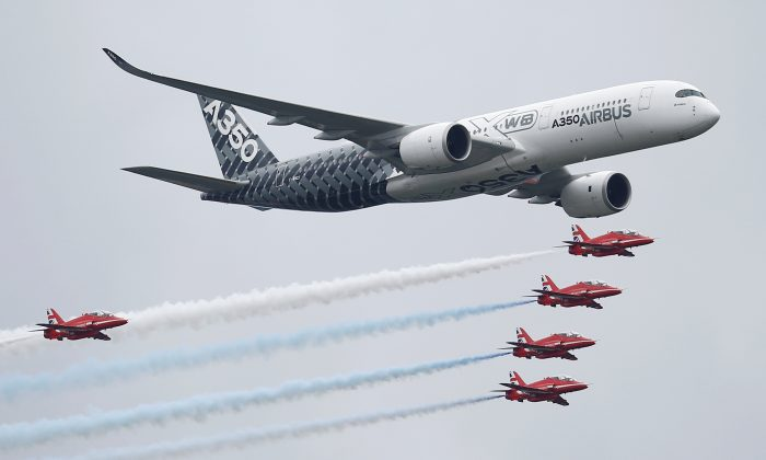 An Airbus A350 aircraft flies in formation with Britain's Red Arrows flying display team at the Farnborough International Airshow in Farnborough, Britain on July 15, 2016.  (REUTERS/Peter Nicholls)
