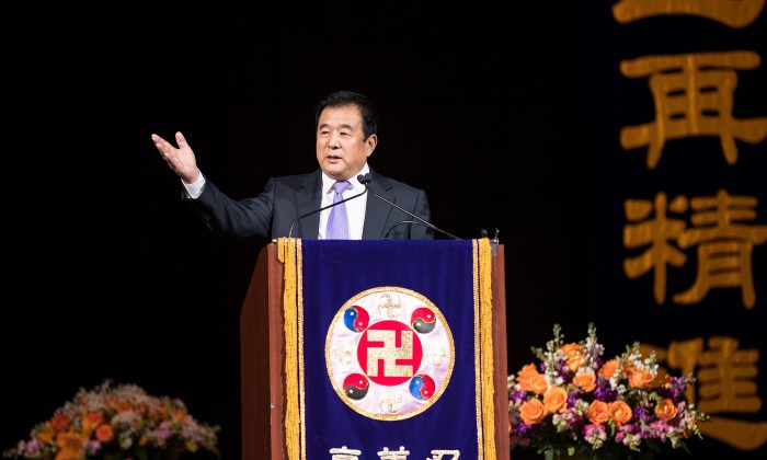 Mr. Li Hongzhi, the founder of Falun Gong, addresses more than 9,000 practitioners of the spiritual discipline at the Capital One Arena in Washington on June 21, 2018. On the podium is the falun, the emblem of Falun Gong, which has at its center the srivatsa, an ancient Buddhist symbol. (Edward Dye/Epoch Times)