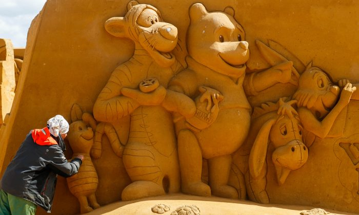 "A sand carver works on a sculpture during the Sand Sculpture Festival ""Disney Sand Magic"" in Ostend, Belgium, on June 21. (REUTERS/Yves Herman)"