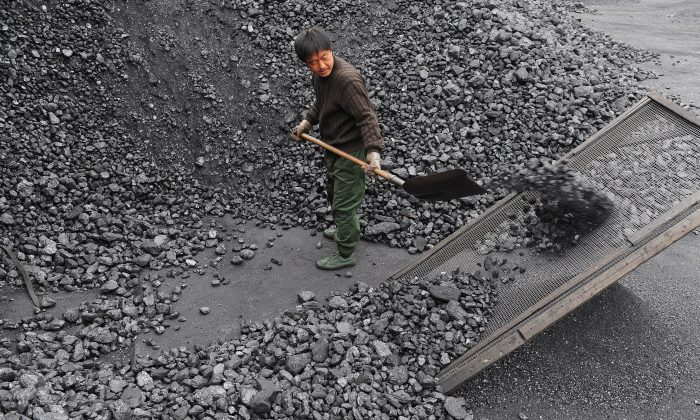 A Chinese worker shovels coal at a mine plant in Hefei, a city in eastern China's Anhui Province, on Dec. 8, 2009. (AFP/AFP/Getty Images)