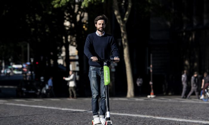 Arthur-Louis Jacquier, director General of Lime France, rides an electric scooter on their launch day in Paris on June 22. (CHRISTOPHE ARCHAMBAULT/AFP/Getty Images)