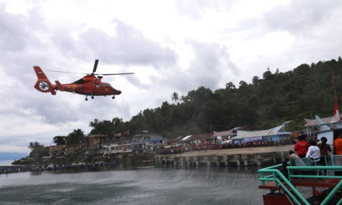 A search and rescue helicopter taking part in the search for a ferry that sank earlier this week in Lake Toba prepares to land at Tigaras port, Simalungun, North Sumatra, Indonesia June 23, 2018 in this photo taken by Antara Foto. Picture taken June 23, 2018.  (Antara Foto/Irsan Mulyadi via Reuters)