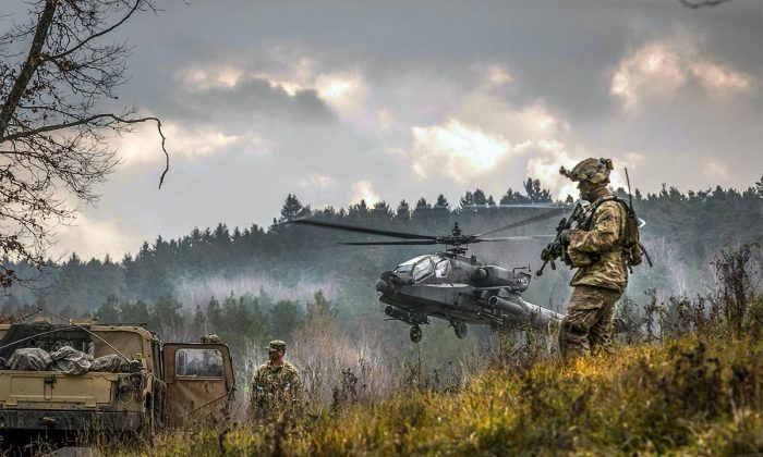 An AH-64 Apache attack helicopter takes off near soldiers participating in the Allied Spirit VII training exercise, Nov. 18, 2017 at Grafenwoehr, Germany. (U.S. Army photo by Spc. Dustin D. Biven)
