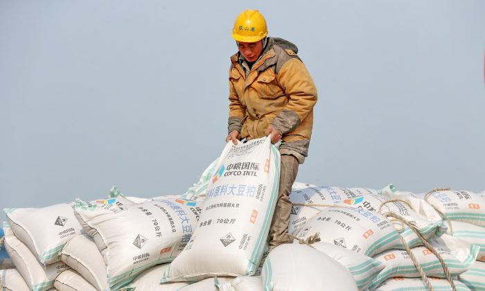 A Chinese worker carries a bag of soybean meal at a port in Nantong, Jiangsu Province, China on March 22, 2018. (AFP/Getty Images)