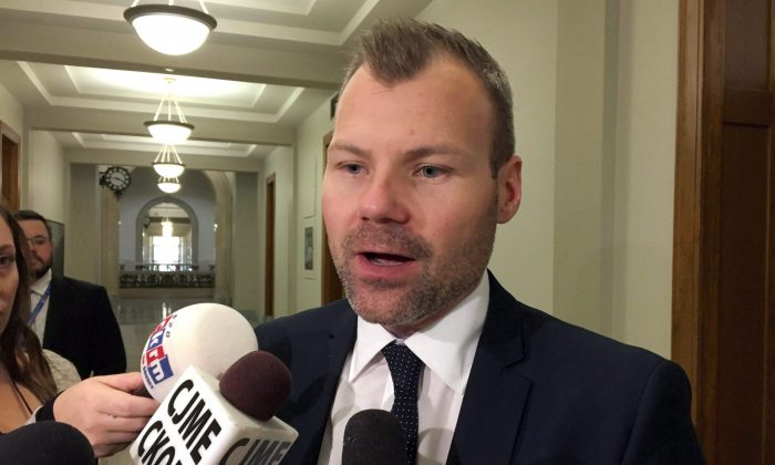 Saskatchewan Energy Minister Dustin Duncan scrums with reporters at the provincial legislature in Regina on Nov. 17, 2016. A study by the University of Regina says the federal carbon tax could potentially reduce Saskatchewan's gross domestic product by almost $16 billion between 2019 and the end of 2030. (The Canadian Press/Jennifer Graham)