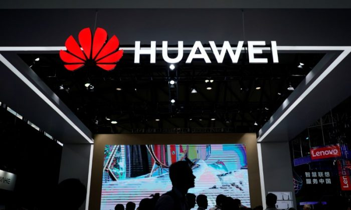People walk past a sign board of Huawei at CES (Consumer Electronics Show) Asia 2018 in Shanghai, China on June 14, 2018. (Aly Song/Reuters)