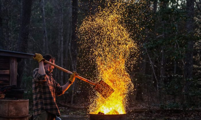 Tuffy Stone tends to a burn barrel, a centuries-old way of burning fresh wood down to hot coals to use for barbecue. (Ken Goodman)