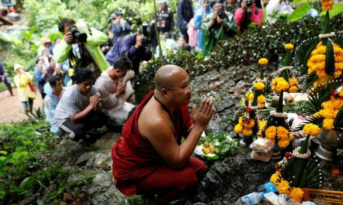 A Buddhist monk and relatives pray near Tham Luang caves during a search for 12 members of an under-16 soccer team and their coach, in the northern province of Chiang Rai, Thailand, June 27, 2018. (Soe Zeya Tun via Reuters)