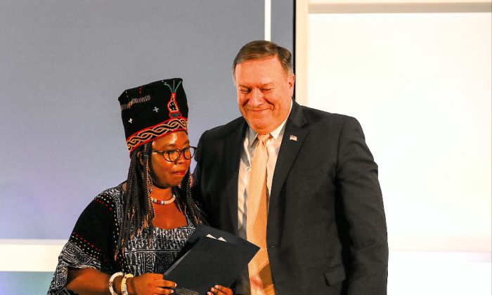 Secretary of State Mike Pompeo embraces Francisca Awah Mbuli after she shared her story of being trafficked, at the State Department in Washington on June 28, 2018. (Charlotte Cuthbertson/The Epoch Times)