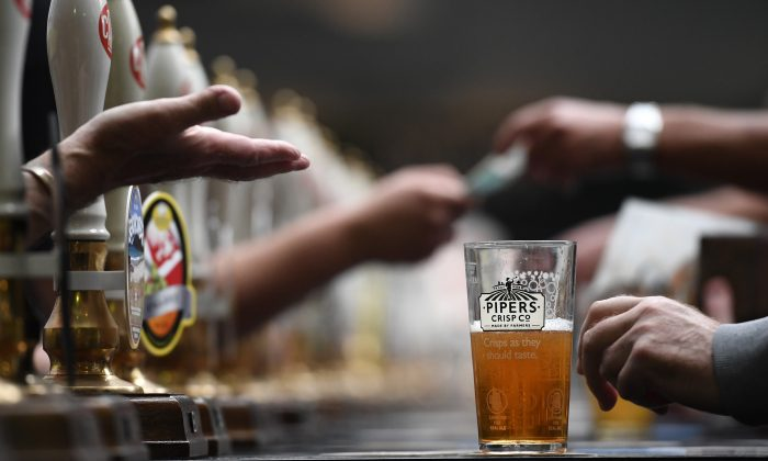 Bar staff serve visitors at the Campaign for Real Ale Great British Beer festival at Olympia exhibition center in London on Aug. 8, 2017. (Carl Court/Getty Images)
