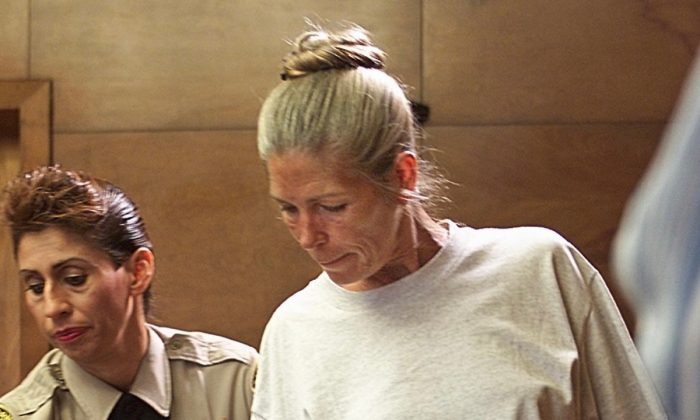 Corrections officer Sandra Fuentes assists Leslie Van Houten as she arrives for her parole hearing before members of the Board of Prison Terms, on  June 28, 2002, at the California Institution for Women in Corona, California.  (Damian Dovarganes/AFP/Getty Images)
