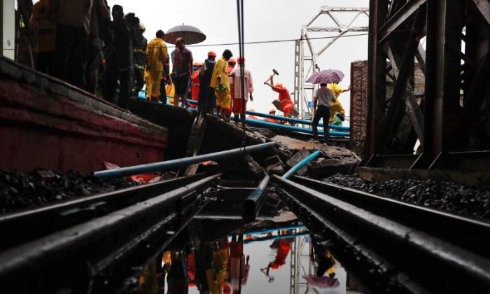 Rescue workers seen working at the site of an overbridge that collapsed over the railway tracks after heavy rains in Mumbai, India on July 3, 2018. (REUTERS/Danish Siddiqui)