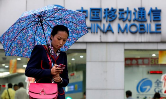 A woman uses her mobile phone in front of a China Mobile office in downtown Shanghai on October 22, 2012. (Aly Song/File Photo/Reuters)