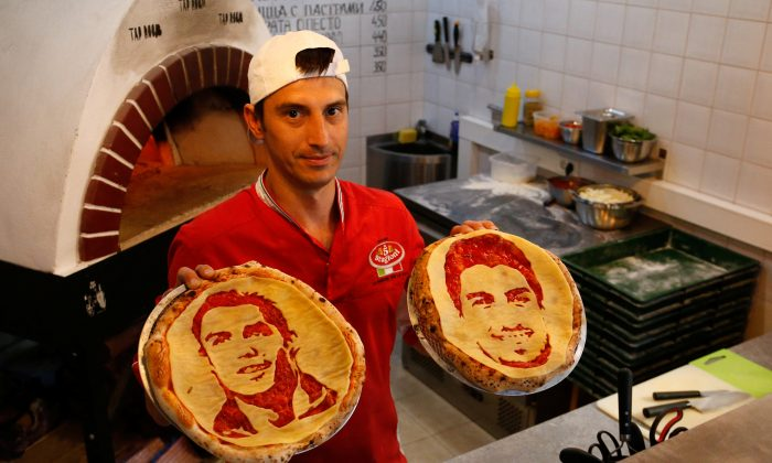 Chef Valery Maksimchik poses with pizzas decorated with portraits of Portugal's Cristiano Ronaldo and Uruguay's Luis Suarez at HopHead Tap Room in St. Petersburg, Russia, on June 29. (REUTERS/Anton Vaganov)