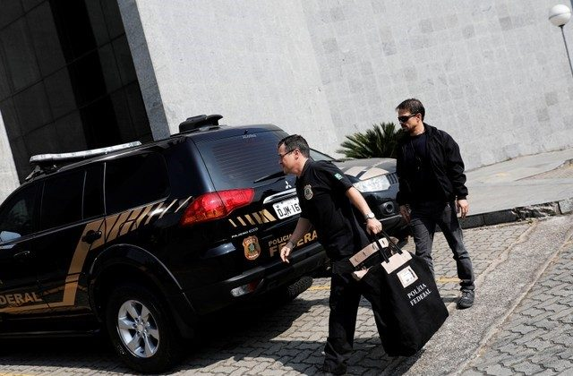 A federal police officer carries a pouch as he arrives at the Federal Police headquarters in Sao Paulo, Brazil on July 4, 2018. (REUTERS/Nacho Doce)