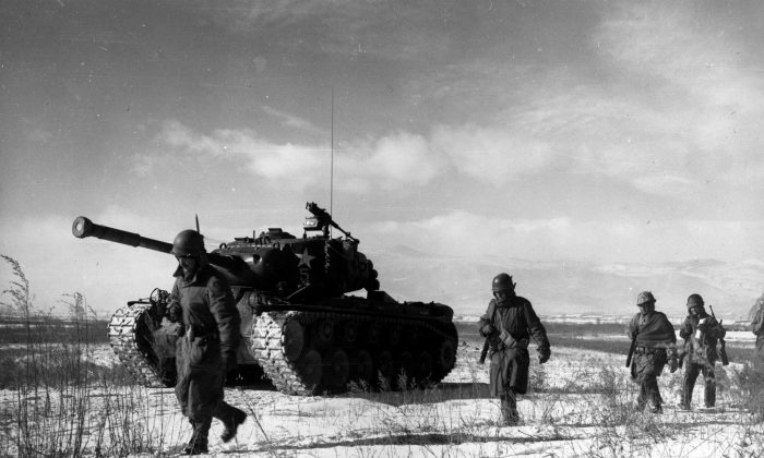A column of troops and armor of the 1st Marine Division move through communist Chinese lines during their successful breakout from the Chosin Reservoir in North Korea during the Korean War. (Cpl. Peter McDonald, US Marine Corps)