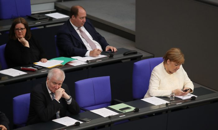 German Chancellor and leader of the German Chistian Democrats (CDU) Angela Merkel (R) and German Interior Minister and leader of the Bavarian Social Union (CSU) Horst Seehofer (L) attend a session of the Bundestag the day after the two leaders reached a hard-wrung compromise over migration policy, on July 3, 2018 in Berlin, Germany. (Sean Gallup/Getty Images)