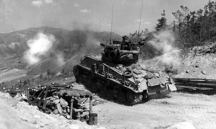 A column of troops and armor of the 1st Marine Division move through communist Chinese lines during their successful breakout from the Chosin Reservoir in North Korea during the Korean War. (Cpl. Peter McDonald/U.S. Marine Corps)