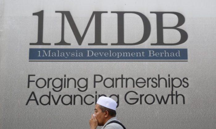 A man walks past a billboard for 1 Malaysia Development Berhad (1MDB), a state investment fund, at its flagship Tun Razak Exchange development in Kuala Lumpur, Malaysia, on February 27, 2015. (Olivia Harris/Reuters)