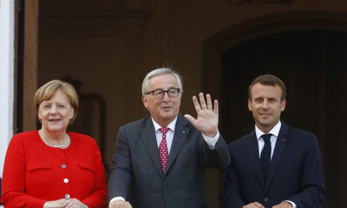 German Chancellor Angela Merkel and French President Emmanuel Macron greet EU commission president Jean-Claude Juncker at Schloss Meseberg governmental palace during German-French government consultations near Gransee, Germany on June 19, 2018. Merkel said on July 5 that she would back lowering EU tariffs on American cars. (Michele Tantussi/Getty Images)