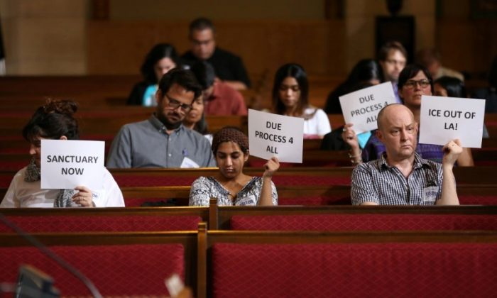 Immigrant supporters protest during the Los Angeles City Council ad hoc committee on immigration meeting to discuss the city's response to threats by the Trump administration to cut funding from Los Angeles and other jurisdictions which federal officials say are providing sanctuary to illegal immigrants arrested for crimes, in Los Angeles, California, on March 30, 2017.  (REUTERS/Lucy Nicholson)