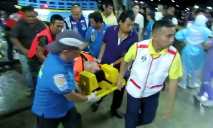Rescuers carry an injured person on a stretcher after a boat capsized off the tourist island of Phuket, Thailand July 5, 2018 in this still image taken from video. Video taken July 5, 2018.  (Reuters via Reuters TV)