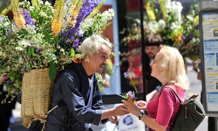 Flower artist Azuma Makoto hands a flower to a lady on June 22, as part of his 30-strong flower messenger procession. (Japan House London)