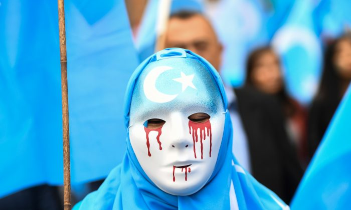 A person wearing a white mask with tears of blood takes part in a protest march of ethnic Uyghurs asking for the European Union to call upon China to respect human rights, during a demonstration around the EU institutions in Brussels on April 27, 2018. (Emmanuel Dunand/AFP/Getty Images)