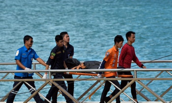 Thai Rescue workers carry the body of a victim on a stretcher, after a boat capsized off the tourist island of Phuket, Thailand, July 6, 2018. (Sooppharoek Teepapan/Reuters)