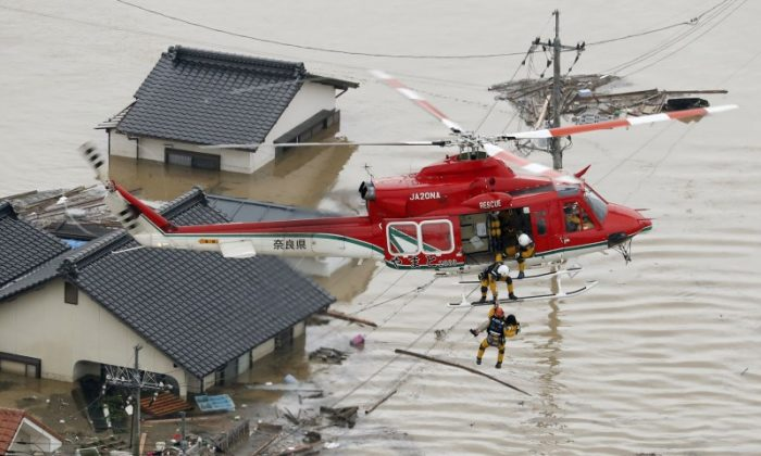 An aerial view shows a local resident being rescued from a submerged house by rescue workers using helicopter at a flooded area in Kurashiki, southern Japan, in this photo taken by Kyodo July 7, 2018. (Kyodo/via Reuters)