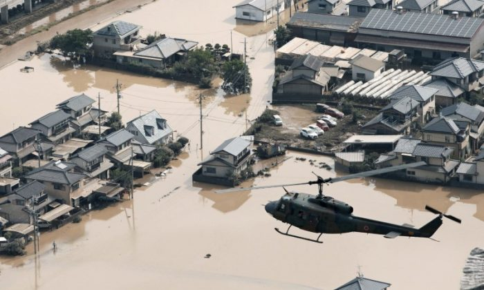 A helicopter flies over Mabi town which was flooded by the heavy rain in Kurashiki, Okayama Prefecture, Japan, in this photo taken by Kyodo July 9, 2018. (Kyodo/via Reuters)