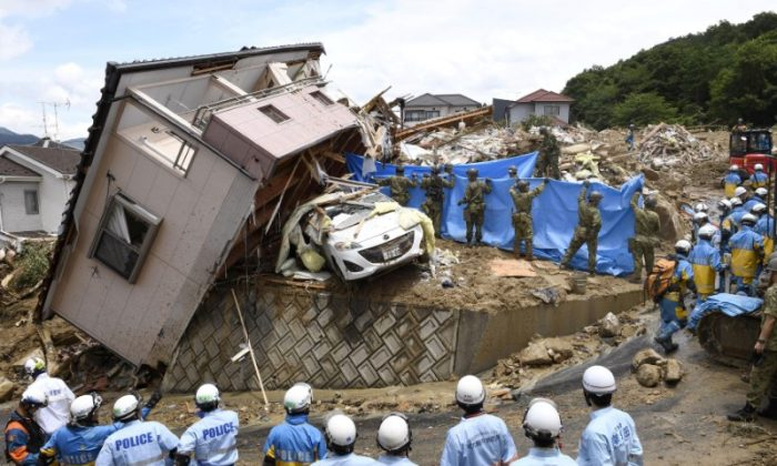 Rescue workers look for missing people in a house damaged by heavy rain in Kumano town, Hiroshima Prefecture, Japan, in this photo taken by Kyodo July 9, 2018. (Kyodo/Reuters)