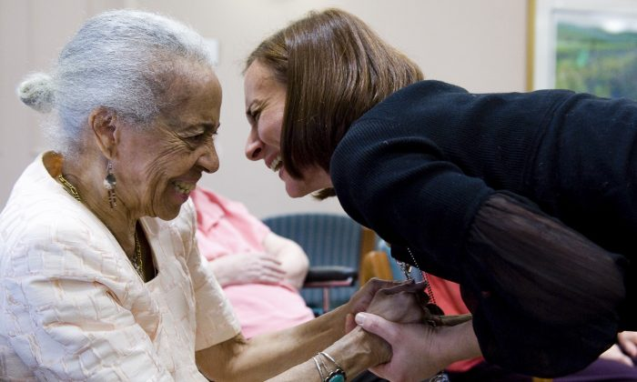 Music therapist Heather Davidson (R) embraces June Thorne after holding a drum circle with patients with Alzheimer's disease at the Copper Ridge Care Center in Sykesville, Maryland, on October 23, 2009. Davidson leads a music therapy session for residents of the center each Friday.          AFP PHOTO/Saul LOEB (Photo credit should read SAUL LOEB/AFP/Getty Images)
