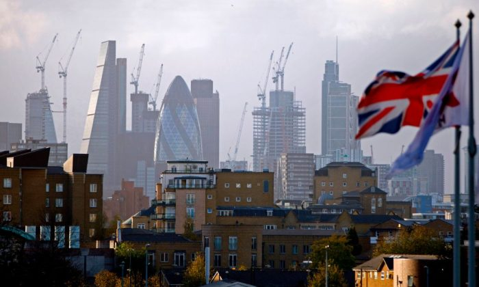 "A Union flag flies from a pole as construction cranes stand near skyscrapers in the City of London, including the Heron Tower, Tower 42, 30 St Mary Axe commonly called the ""Gherkin"", the Leadenhall Building, commonly called the ""Cheesegrater"", as they are pictured beyond blocks of residential flats and apartment blocks, from east London on Oct. 21, 2017. / AFP PHOTO / Tolga AKMEN        (Photo credit should read TOLGA AKMEN/AFP/Getty Images)"