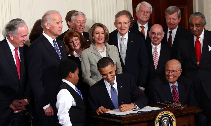 President Barack Obama signs the Affordable Health Care Act during a ceremony with fellow Democrats at the White House on March 23, 2010. (Win McNamee/Getty Images)
