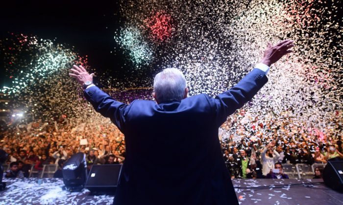 "Newly elected Mexico's President Andres Manuel Lopez Obrador (C), running for ""Juntos haremos historia"" party, cheers his supporters at the Zocalo Square after winning general elections, in Mexico City, on July 1, 2018. (Pedro Pardo/AFP/Getty Images)"