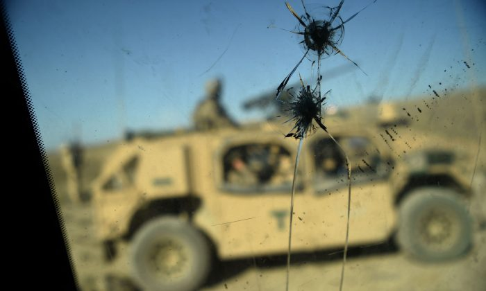 In this photo taken on July 7, 2018, US Army soldiers from NATO are seen through a cracked window of an armed vehicle in a checkpoint during a patrol against Islamic State militants at the Deh Bala district in the eastern province of Nangarhar Province. (Wakil Kohsar/AFP/Getty Images)